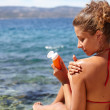 Stock Photo: Woman applying sun protection lotion