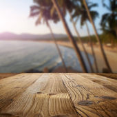 Wooden table on the beach with palms — Stock Photo