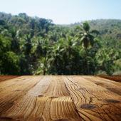Деревянный стол на пляже с пальмами — Стоковое фото