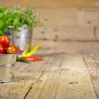 Tomatoes, chives and chili peppers on a wooden table top — Stock Photo