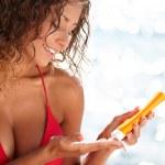 Woman in bikini smear protective cream on the skin — Stock Photo #42380025