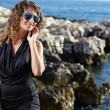 Stock Photo: Woman in a black dress on the ocean coast