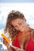 Woman in bikini smear protective cream on the skin — Stock Photo