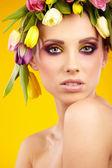 Portrait of a beautiful spring girl wearing flowers hat. Studio  — Stock Photo
