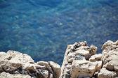 Stones in a blue sea — Stock Photo