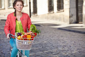 Woman with bicycle and groceries — Stock Photo