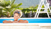 Woman relaxing in a swimming pool — Stock Photo