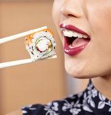 Mujer comiendo sushi con los palillos — Foto de Stock