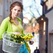 Woman holding bicycle with flowers — Stock Photo #46190405