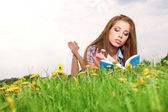 Woman on green field reading book — Stock Photo