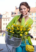 Woman holding bicycle with flowers — Stock Photo