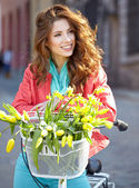Girl on bicycle with spring flower — Stock Photo