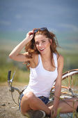 Girl sitting next to bike — Foto Stock