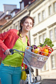 Spring woman with bicycle and groceries — Stock Photo