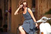 Girl on scooter in old Italian town — Stock Photo