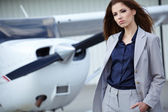 Businesswoman  in front of airplane — Stock Photo