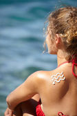 Girl back with sun lotion — Stock Photo