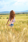 Woman walking on field of grain — Stock Photo