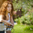 Woman with bike in a country road — Stock Photo #49622745
