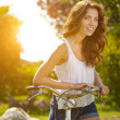 Woman with bike in a country road — Stock Photo #49622751
