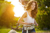 Woman with bike in a country road — Stock Photo