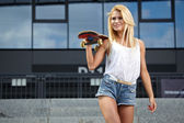 Young woman with skateboard in city — Stock Photo