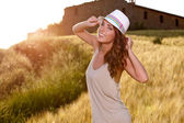 Portrait of a woman on golden cereal field in summer — Stock Photo