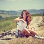 Vintage girl sitting next to bike — Stock Photo