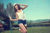Woman having fun in summer garden — Stock Photo