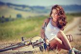 Vintage girl sitting next to bike — Stock Photo