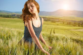 Woman on golden cereal field — Stockfoto