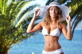 Woman holding her hat at beach — Stock Photo