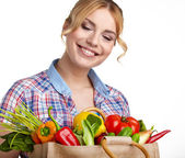 Woman holding shopping bag full of groceries — Stock Photo