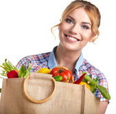 Woman holding shopping bag full of groceries — Stockfoto