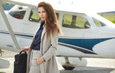 Woman against private jet at airport terminal — Stock Photo
