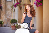 Italian woman sitting on a italian scooter — Stockfoto