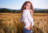 Woman in golden wheat — Stock Photo