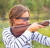 Uma jovem com uma arma para atirar armadilha — Fotografia Stock