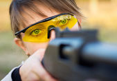A young girl with a gun for trap shooting and shooting glasses — Stock Photo
