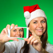 Royalty-Free Stock Photo: Girl in a Christmas hat on a green background