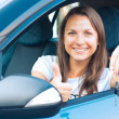 Lady sitting in a car and showing key — Stock Photo