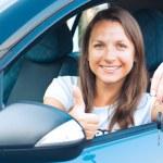Signora seduto in una macchina e mostrando la chiave — Foto Stock
