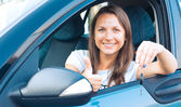 Dame assis dans une voiture et montrant la clé — Photo