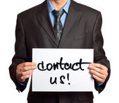 Young businessman points on a card Contact Us on a white — Stock Photo