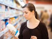 Mladá dívka v supermarketu s potravinami — Stock fotografie