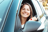 Leende flicka sitter i en bil och visar nyckel — Stockfoto