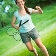 Smiling girl with a racket for a badminton in the park - 图库照片