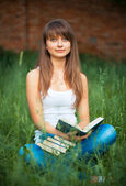 Female student with books on grass outdoors — Stock Photo