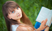 Beautiful girl with book in the park on green grass — Stock Photo