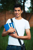 Arab male student with books outdoors — Stock Photo